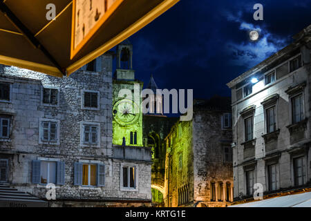 Peoples Square with the tower of the Split Cathedral behind lit up under a full moon in Split Croatia - Stock Photo