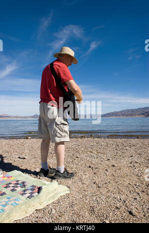 Man plays guitar on beach at Lake Mead National Recreation Area Nevada, USA. - Stock Photo