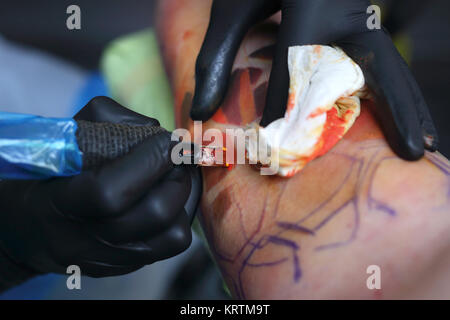 tattoo studio. tatoo drawing on his shoulder. large color tattoo. - Stock Photo