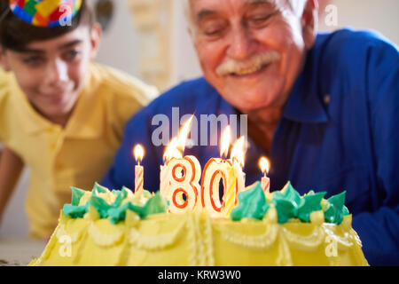 Boy and Senior Man Blowing Candles On Cake Birthday Party - Stock Photo