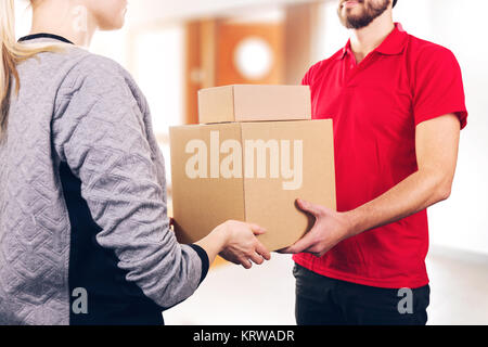woman accepting a delivery of boxes from delivery service courier - Stock Photo