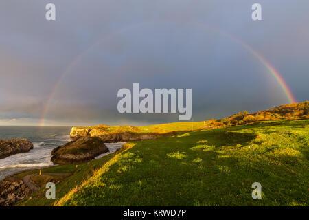 Rainbow over the Asturian coast, near Cue. Spain. - Stock Photo