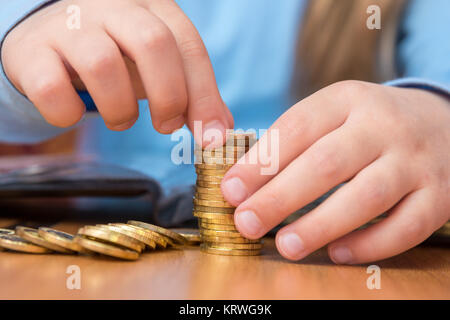 Child collects a stack of golden coins, close-up - Stock Photo