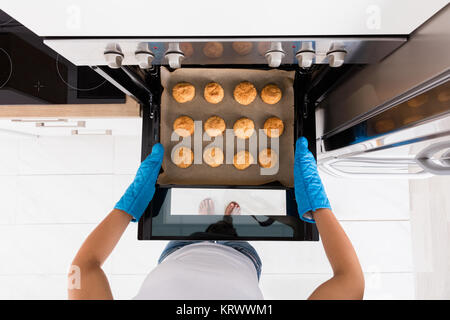 Woman Baking Cookies In Oven - Stock Photo