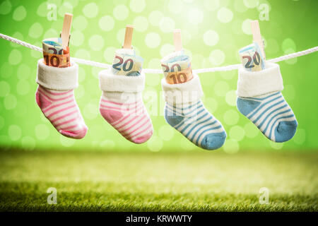 Pair Of Baby Sock With Dollar Hanging On Rope - Stock Photo