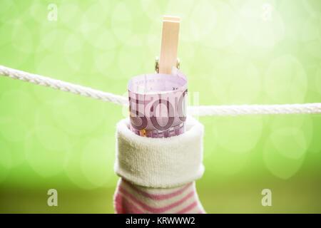 Baby Sock With Dollar Hanging On Rope - Stock Photo