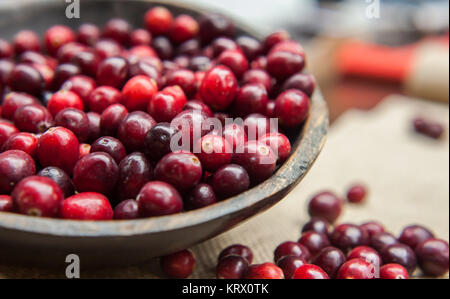 Fresh cranberries in rustic wooden bowl on burlap Background an - Stock Photo
