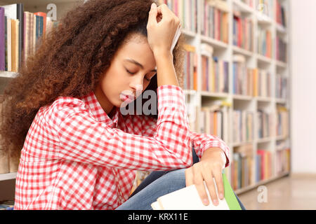 girl reading a book in a bookstore. young woman reading an interesting book in the bookstore. antique shop. university - Stock Photo