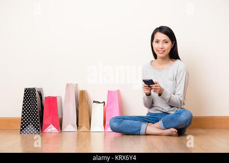 Woman using the cellphone for shopping online - Stock Photo