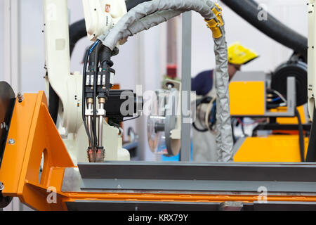 Industrial welding robot arm in the focus, blurred welder in the background - Stock Photo