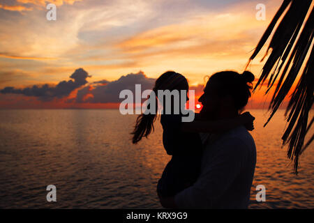 Silhouette of father and daughter on the beach at dusk. - Stock Photo