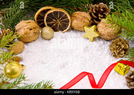Christmas decoration with different nuts and golden star isolated on snow background. Christmas background. - Stock Photo