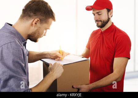 delivery service - man signing delivery receipt of box - Stock Photo
