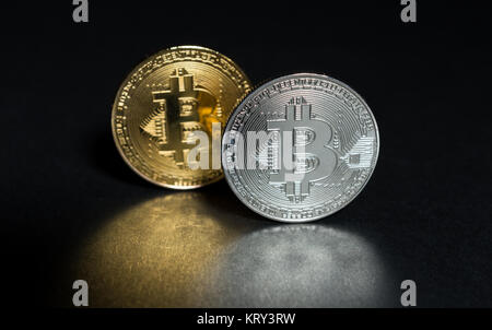 Two bitcoins golden and silver isolated on dark black background with beautiful reflection - Stock Photo