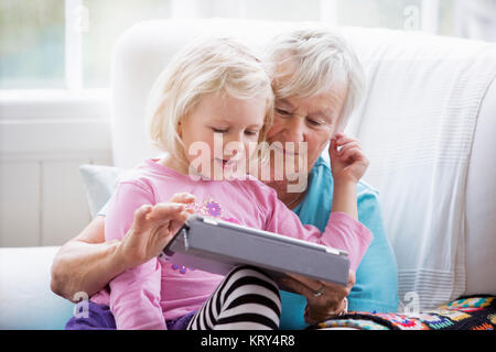 Grandmother and Granddaughter looking at a tablet - Stock Photo