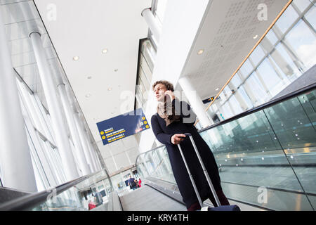 A woman talking on her cell phone in the Stockholm Arlanda Airport - Stock Photo