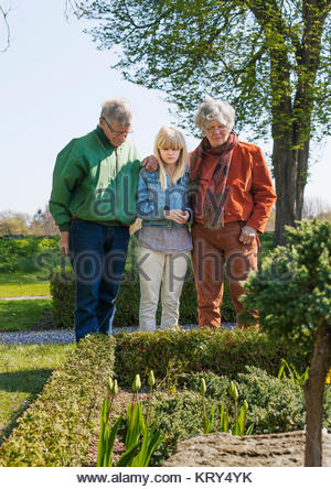 Girl and her grandparents in churchyard garden - Stock Photo