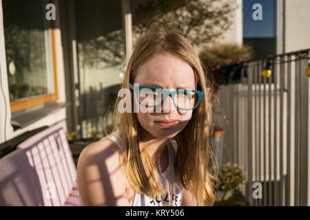 A young girl wearing glasses sitting outside - Stock Photo