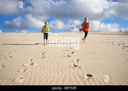 Two children running along the beach - Stock Photo