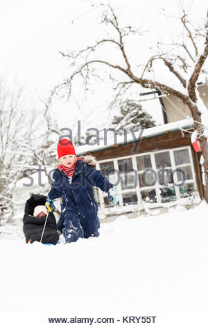 Boy pulling his sister in a sled - Stock Photo