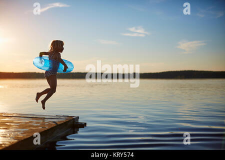 Girl jumping off a pier - Stock Photo