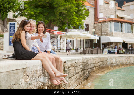 A mother and two daughters sitting on a wall above the sea - Stock Photo