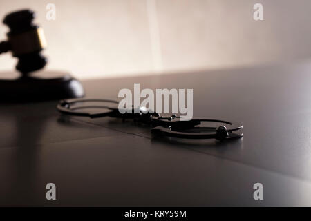 Criminal law concept. Cuffs and jugde gavel on stone background. - Stock Photo
