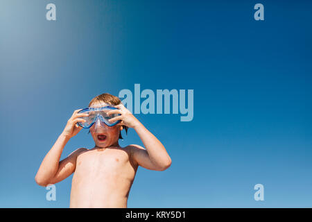 A young boy wearing swim goggles - Stock Photo