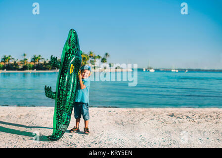 A young boy at the beach with an inflatable crocodile - Stock Photo