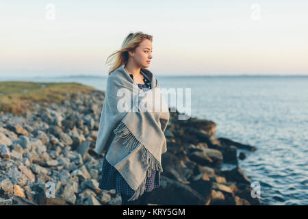 A young woman wrapped in a shawl looking out to sea - Stock Photo