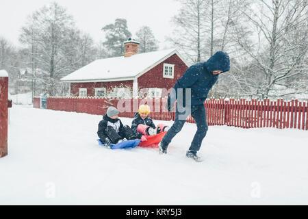 Man pulling children on sled - Stock Photo