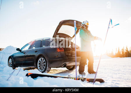 Man by a car with skiing equipment in Osterdalen, Norway - Stock Photo
