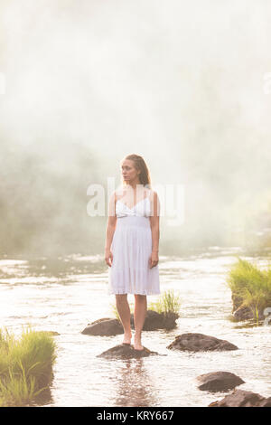 Woman wearing a white dress standing in river - Stock Photo