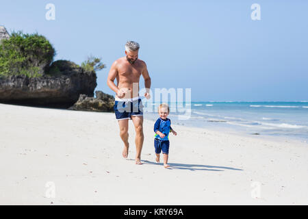 Father and son running on Diani Beach, Kenya - Stock Photo