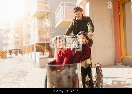 Man cycling with his sons in Stockholm - Stock Photo