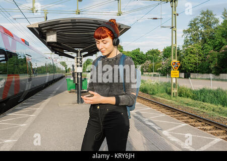 Woman wearing headphones on train platform - Stock Photo