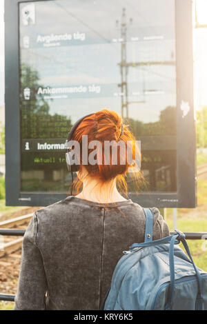 Woman wearing headphones by train sign - Stock Photo