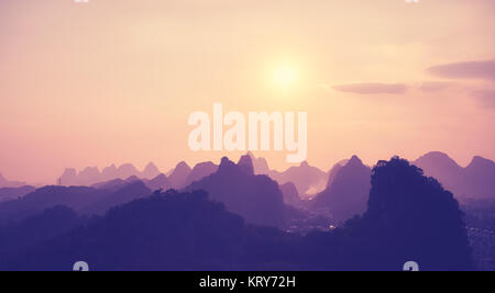 Color toned scenic sunset over Karst mountains in Guilin, China. - Stock Photo