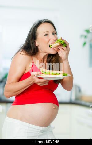 Schwangere Frau isst ein Sandwich - pregnant woman eats a sandwich - Stock Photo