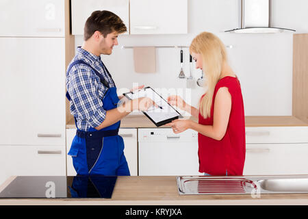 Male Plumber Showing Woman To Sign The Invoice - Stock Photo