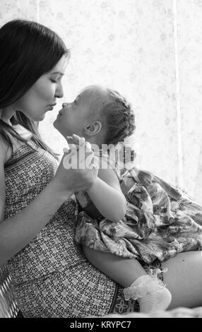 A young mother with her daughter relaxing on a summer terrace. Mom kisses her little daughter. - Stock Photo
