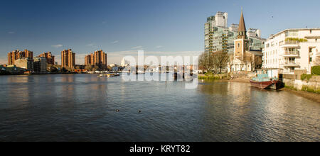 London, England, UK - March 16, 2014: Sun shines on the tower and west face of Battersea Church and apartment buildings - Stock Photo