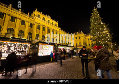 Traditional christmas market with illuminated Schönbrunn palace and fairy lights decorated Christmas tree at dusk, - Stock Photo
