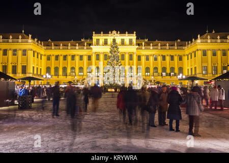 View of illuminated Schönbrunn palace in Christmas time with fairy lights decorated Christmas tree at dusk in Advent. - Stock Photo