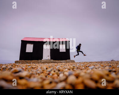 A woman leaps from the side of a small black and red hut on the riverbank in Rye Harbour Nature Reserve, East Sussex - Stock Photo