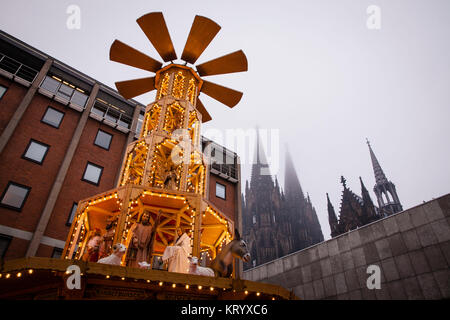 Europe, Germany, Cologne, big christmas pyramid on the christmas market at the cathedral, light fog.  Europa, Deutschland, - Stock Photo