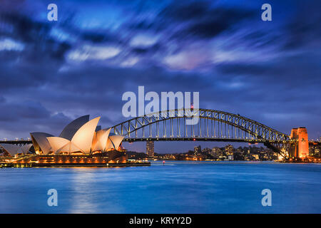 Sydney, Australia, 18 March 2017: World famous Sydney Opera House and Harbour bridge at sunset. Blurred clouds and - Stock Photo