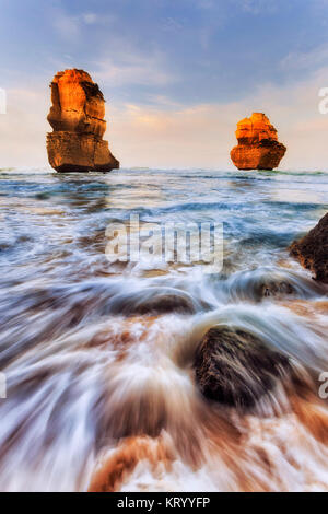 Two limestone eroded disconnected apostle rocks off Gibson Steps sandy beach on Twelve Apostles marine park at sunrise. - Stock Photo