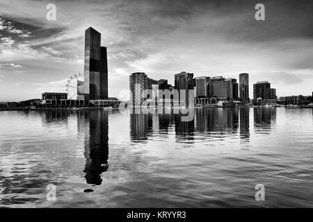 Black white dramatic view of modern Docklands residential high-rise towers and amusement observation wheel reflecting - Stock Photo