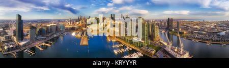 Wide panorama of Docklands modern suburb in Melbourne on Yarra river from amusement wheel to city CBD waterfront - Stock Photo